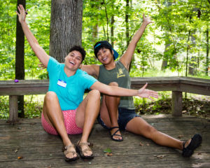 counselors Chris and Kaley seated on the floor of a wood platform in the forest, arms outstretched and faces smiling