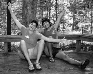 grayscale counselors Chris and Kaley seated on the floor of a wood platform in the forest, arms outstretched and faces smiling