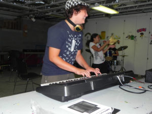 A camper in a checkered hat delightedly plays the keyboard; inthe background, another camper dances with a handkerchief, and another plays a drumset