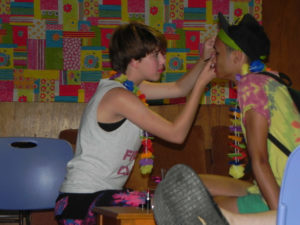 One campers helps another apply eye makeup in a. quiet corner; both are wearing novelty lei necklaces