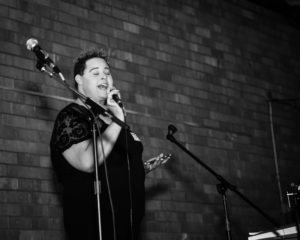 grayscale camper sings passionately into a mic while on stage in front of a brick backdrop