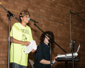 "2 campers perform on stage, one seated at a keyboard watching the standing camper at the mic with a crumpled paper in hand; they wear a fluorescent yellow QORDS t-shirt featuring an illustration of a squirrel-camper and the word ""YASSSS!"""