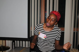 DJ Femi the Femme grooves to music in a striped t-shirt and red bandana headwrap