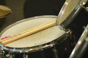 close up of a snare drum and drumsticks resting on top