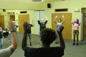"""campers participate in an indoor """"ice-breaker"""" activity, positioned in a circle with arms in the air"""
