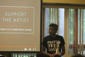 """Counselor Femi leads a workshop, mouth open in the middle of speaking. They wear a t-shirt declaring """" PEOPLE OVER MONEY"""" and the projector behind features a slide stating """"SUPPORT THE ARTIST"""""""