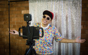counselor in sunglasses and cap poses with arms outstretched between a glittery backdrop and a camera tripod