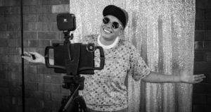 grayscale counselor in sunglasses and cap poses with arms outstretched between a glittery backdrop and a camera tripod