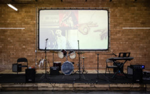 empty band stage featuring mic stands, a drum set, keyboards, amps, and a wall projection screen