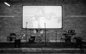 grayscale empty band stage featuring mic stands, a drum set, keyboards, amps, and a wall projection screen