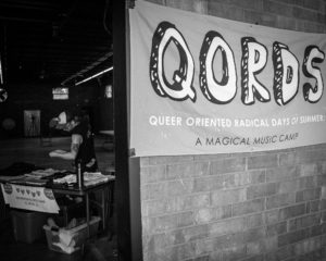 grayscale outer brick wall donning QORDS banner; seen around left edge of wall a counselor readies the merch table at the entrance of the performance space