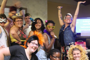 10 campers and staff gathered closely together in costumes and silly outfits such as mini cowboy hats, lion's manes, and pinwheel hair accessories