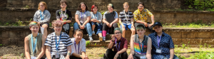 13 campers seated in two rows on low brick walls. All wear lanyards and many have colored hair